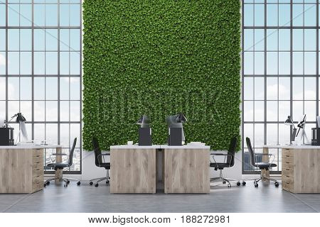 Open office with wooden desks computers on them a grass wall and tall skyscraper windows. 3d rendering mock up