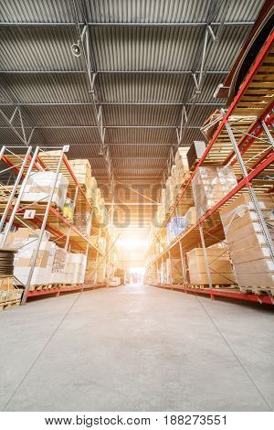 Large industrial warehouse. Long shelves with a variety of boxes and containers. Bright sunlight.