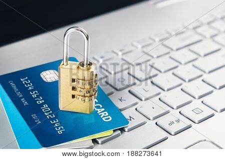 Laptop with padlock and credit cards on keyboard. Computer systems security concept
