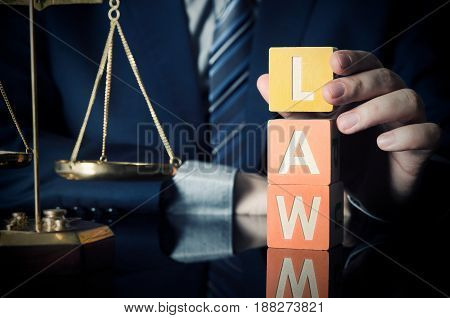 The lawyer puts LAW word. Attorney and lawyer concept. lawyer law justice judge scales courtroom blocks toy concept