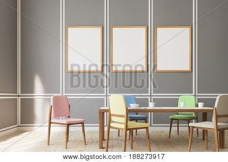 Three medium size vertical posters are hanging on gray living room walls with chairs of different colors near a wooden table table. 3d rendering mock up