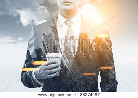Close up of a young businessman with a paper cup of coffee standing against a blue sky with shining sun. There is a cityscape in the foreground. Toned image double exposure
