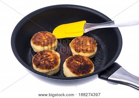 Fried cheese cakes in frying pan. Studio Photo