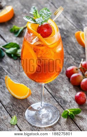 Fresh fruit tropic cocktail with mint orange and grapes in tall glass on wooden background. Summer drinks and alcoholic cocktails.
