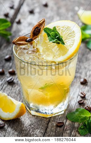 Cold alcoholic cocktail with lemon lime and mint in glass on wooden background. Summer drinks.