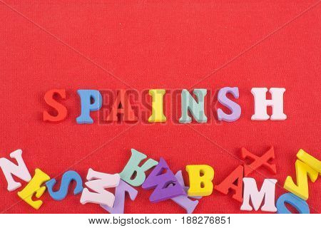 SPAIN word on red background composed from colorful abc alphabet block wooden letters, copy space for ad text. Learning english concept