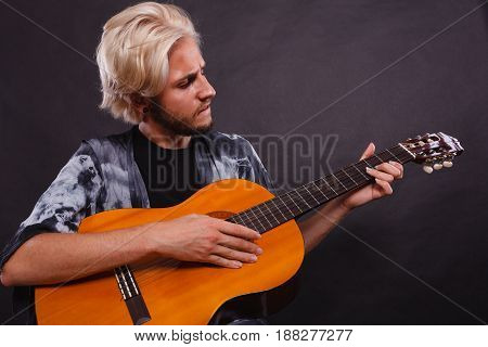 Music passion concept. Young blonde man wearing fancy shirt playing on acoustic guitar studio shot black background.