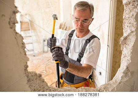 Adult Senior Worker Builder Using Hammer And Smash Tool