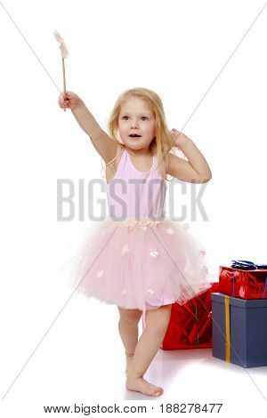 Adorable little Princess with a magic wand in the hands is surrounded by a beautifully Packed boxes with gifts. In the Christmas holiday. A girl waves a magic wand , she casts a magic spell.Isolated.