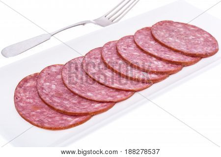 Slices of salami on white plate. Studio Photo