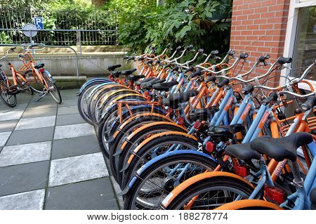 AMSTERDAM NETHERLANDS - MAY 14 2017: Parking of rental bicycles near the youth hostel