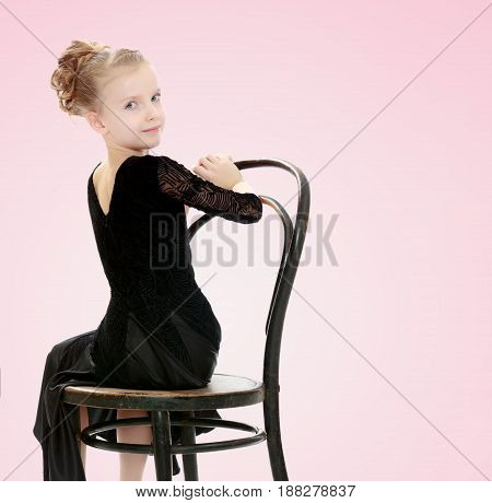 The slender little blonde girl dancer in the long dress of black color made specifically for performing .Girl sitting on an old Viennese chair and looking at the camera over his shoulder.