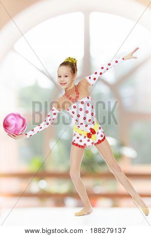 Beautiful little girl gymnast dressed in sports suits for competition, performs exercises with the ball.In a room with a large semi-circular window.