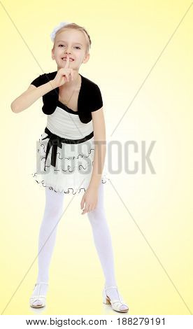 Beautiful little blonde girl dressed in a white short dress with black sleeves and a black belt.Girl keeps the index finger around the lips . The gesture of silence.On a yellow gradient background.