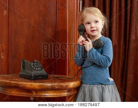 The little girl in the interior of the fifties of the last century keeps the ear-hook of vintage phone. The girl calls her grandmother.