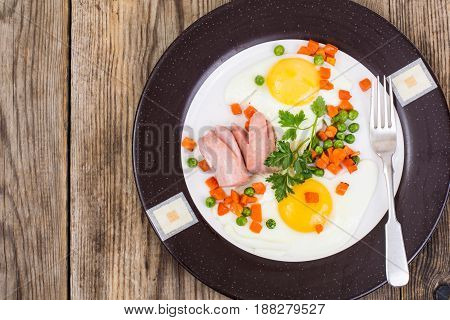 Plate with fried eggs and steamed vegetables for breakfast. Studio Photo