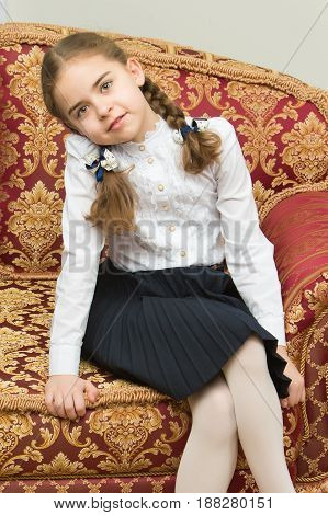 A lovely little blond girl, with long braided hair in braids, sits on the couch.