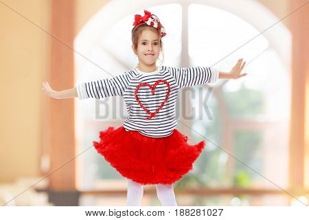 Little girl in a red skirt and bow on her head.She poses with her arms out to the sides.In a room with a large semi-circular window.