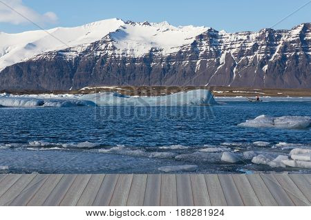 Opening wooden floor Winter lagoon with black rock mountain background Iceland winter season natural landscape