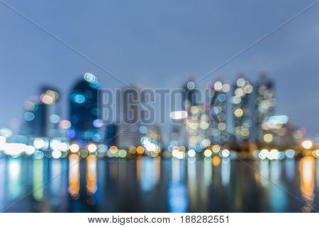 Beauty of blurred bokeh light office building with water reflection abstract background