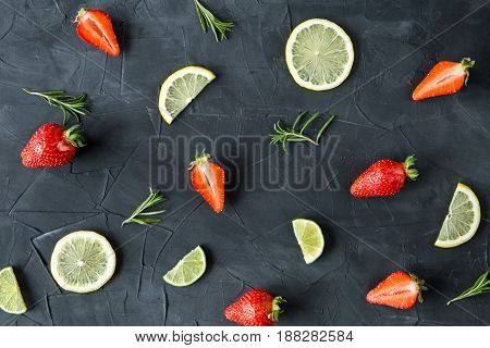 Fresh strawberries, lime slices and rosemary on concrete background. top view