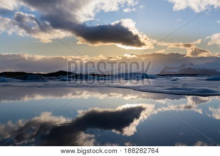 Reflection winter lagoon with sun behind white clouds Iceland winter natural landscape background