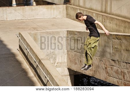 Young man jumping from a great height. Parkour in the urban space. Sports in the city. Sport activity.