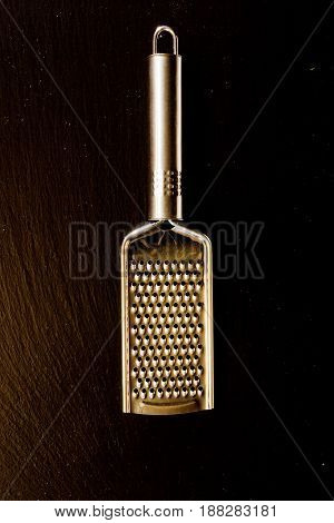 Metallic shiny grater on a black background