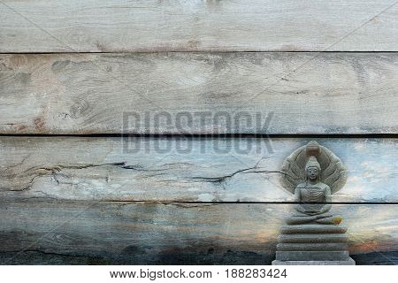Overlay the outdoor beautiful stone Buddha Image covered with seven heads of Naka (Great Snake) on Told wood texture.