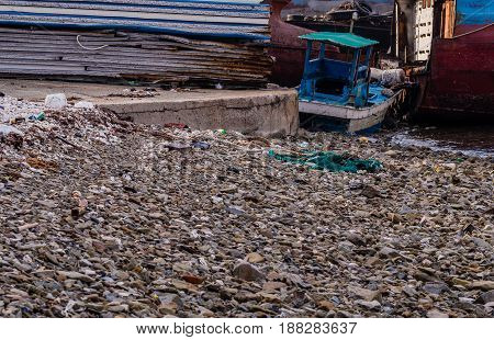 Old rusty abandoned ships sitting on the shore amid trash and debris at a marine junkyard in South Korea