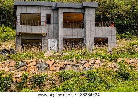 Unfinished abandoned gray concrete house in the side of a hill with stone wall in the foreground and lush green foliage in the background.
