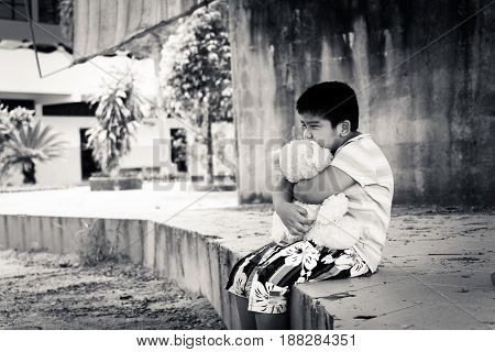Cute asian boy crying alone in the park black and white tone