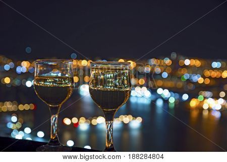 beautiful night scenery, goblets with drink stand in the background of the city at night, and the bridge with lights