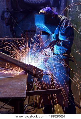 Industrial worker welding in factory