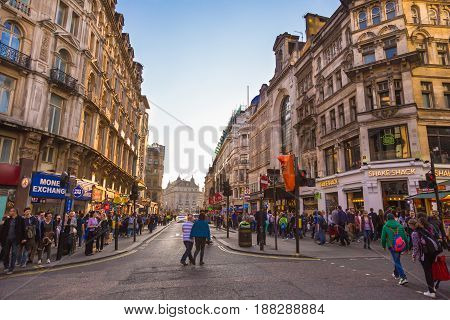 London England - 9 April 2017 - Many people walk around a busy area of London England on Sunday evening April 9 2017