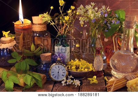 Natural still life with candle, bottles, healing herbs and flowers. Alternative medicine vintage concept