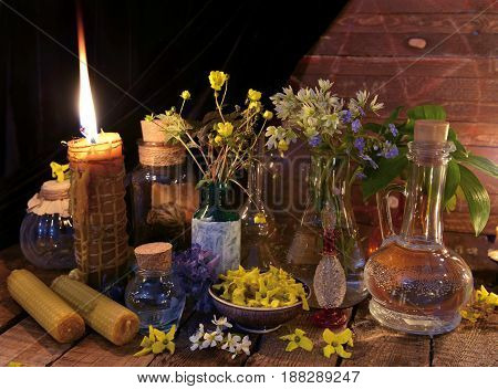 Retro still life with candles and flowers in glass bottles against wooden background. Alternative medicine vintage concept