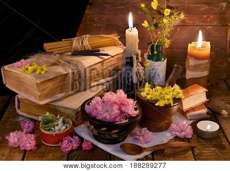 Still life with old book, healing herbs, flowers and candles. Alternative medicine vintage concept