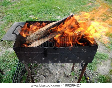 Photo of fire brown wood dark grey black coals on bright yellow fire inside metal brazier.Wood burning in the braziers.Flames fires preparation for cooking barbecue.Brazier of nature bbq background.