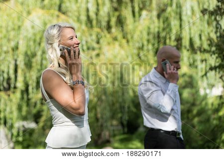 Couple talking on mobile or smart phone. Man and woman speak with telephone. Young people use cellphone for call in park. Business talk with smartphone in garden green nature trees background.