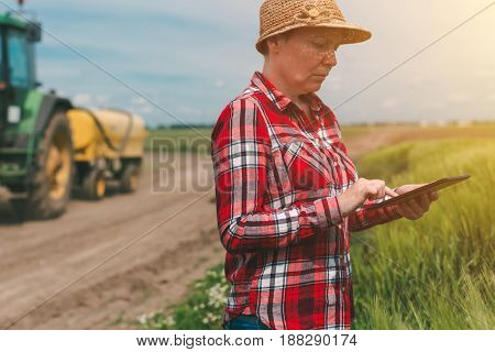 Using modern technology in agricultural activity female farmer agronomist with digital tablet computer using mobile app in wheat crops field tractor with crop sprayer in background