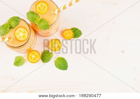 Freshly blended orange citrus kumquat fruit smoothie in glass jars with straw mint leaf cute ripe berry top view. White wooden board background copy space.