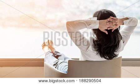 Business woman lifestyle at home sitting on modern chair in living room looking out of window toward beautiful cityscape downtown urban river landscape city life w/ sunlight effect: Easy happy people; Shutterstock ID 448063051; PO: today.com