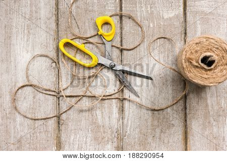 Scissors and rope on wooden background. Top view on workplace with diy tools. Decoration equipment, florist, decorator, handmade concept.
