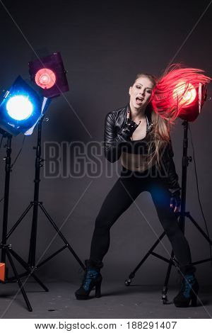 Girl In A Leather Jacket On Stage And Colored Spotlights