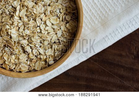 Oat flakes or oatmeal in wood bowl put on rustic wood table. Rolled oat is clean food for health. Prepare oat flakes for bakery or cooking. Natural organic food in top view.