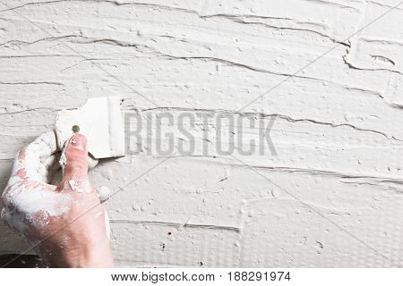 Builder dirty hand with spatula spread white stucco on wall. Plastering work, house repair background with free space for text.