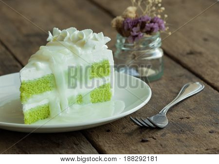 Pandan cake frosting with whipped cream topping with young toddy palm seed in coconut milk sauce on white plate put on rustic wood table. Thai style dessert. Thai style cake. Triangle slice piece of pandan cake.