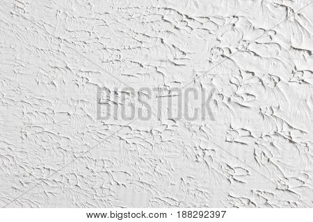 White grungy relief background, rough surface. Backdrop of plastered wall with free space for text.