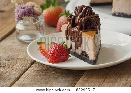 Homemade chocolate cheesecake on rustic wood table. Baked chocolate cheesecake topping brownie and dark chocolate sauce decoration with strawberry. Triangle slice piece of cheesecake on white plate.
